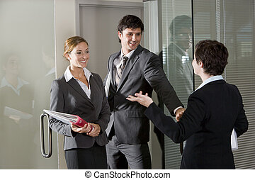 Three office workers chatting at door of boardroom - Three ...