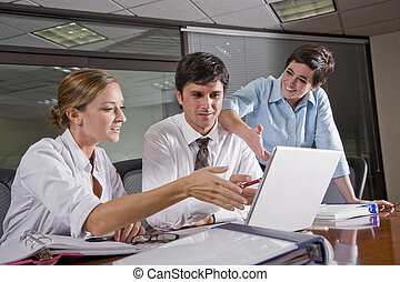 Three office workers working in boardroom - Three office...