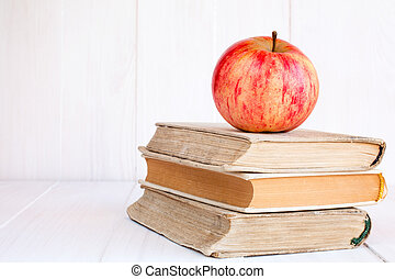 Three old  books with red apple