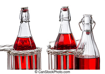 Three old bottles with red juice