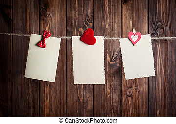 three old paper sheet with bow and hearts hanging on...