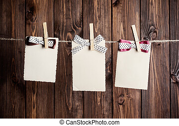 three old paper sheets with bows hanging on clothesline...