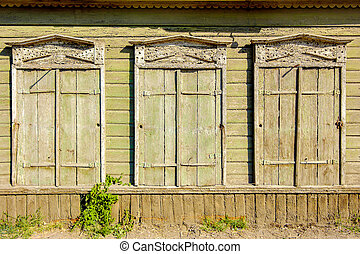Three old vintage windows in traditional Russian style in Astrakhan, Russia. Front view, closed shutters