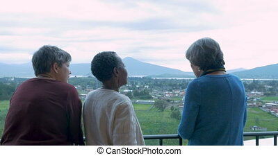 Three older women in 60s talking at an scenic overlook -...