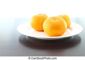 Three orange dish on wooden table.