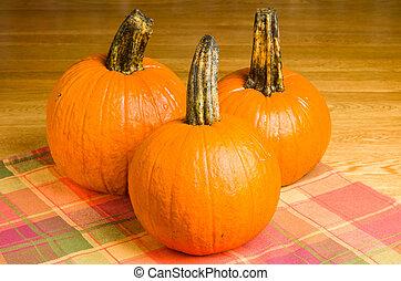Three orange pumpkins on a wooden table