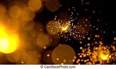 Three orange sparklers against dark background. Super slow...
