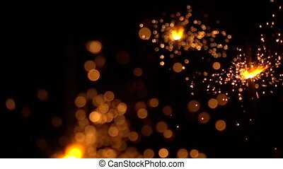 Three orange sparklers against dark background. Super slow motion shallow focus video, 500 fps