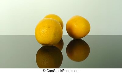 Three oranges falling down on a reflecting surface, 2 videos...