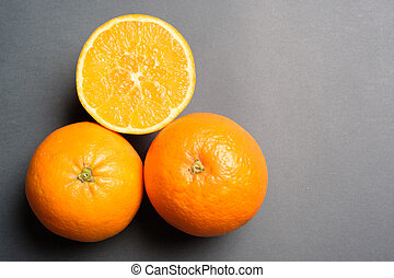 Three oranges on grey background