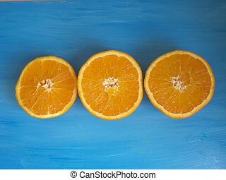 Three oranges split in half isolated on a blue background