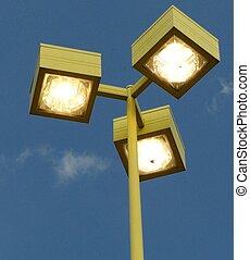 THREE OUTDOOR LIGHTS - Three outdoor lights against a blue...