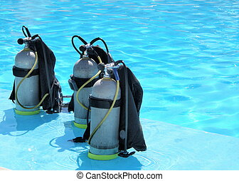 three oxygen tanks in the shallow part of a pool