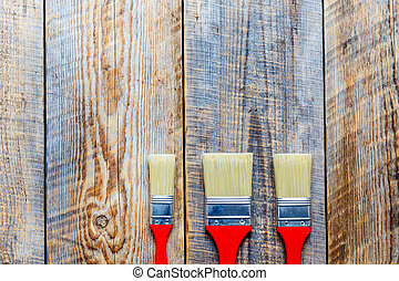 three paint brush on wooden floor top view