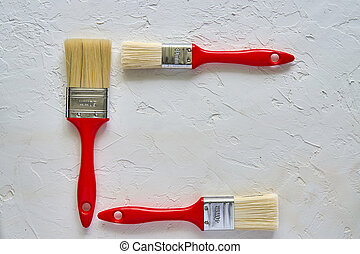 three paintbrushes with red handles on freshly made concrete background. Repairing concept. Top view with copy space