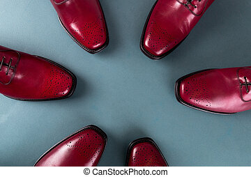 Three pair brogues in a circle. Red oxford shoes on blue...