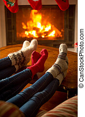 Three pair of feet in socks warming at burning fireplace at house