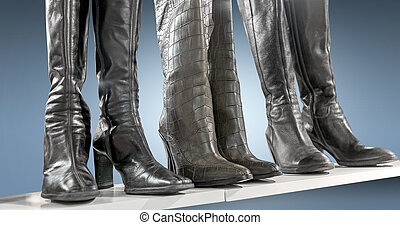 Three pairs of boots on blue background