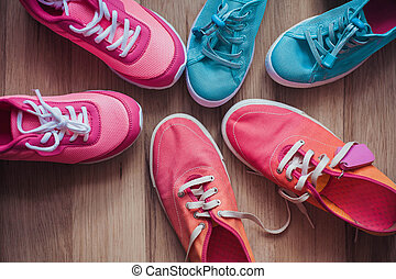 Three pairs of colorful sneakers on a wooden background.
