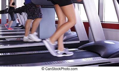 Three pairs of legs walking on the running track