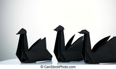 Three paper swans on white background.