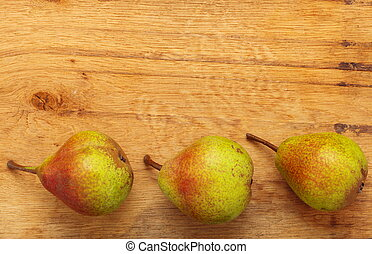 Three pears fruits on wooden table background - Three pears ...