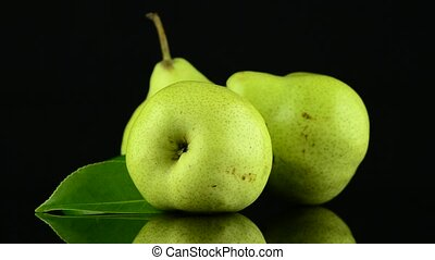 Three pears rotating on black reflective background.