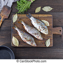 three peeled river fish with spices