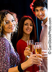 Three people are holding the glasses of champagne and...