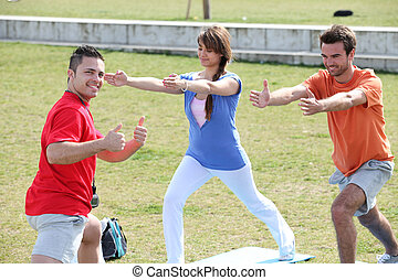 Three people doing yoga in a park