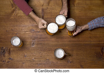 three people drinking beer at the wooden table at pub
