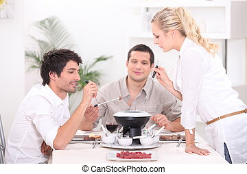 Three people enjoying fondue