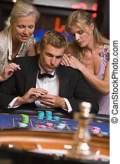 Three people in casino playing roulette smiling (selective focus)