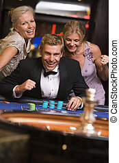 Three people in casino playing roulette smiling (selective...