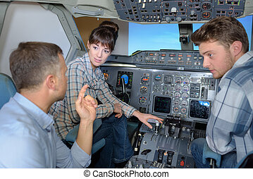Three people in cockpit of aircraft