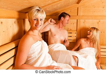 Three people in sauna - Three people (one male, two female)...