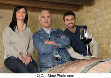 Three people in wine cellar