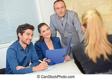 Three people interviewing lady