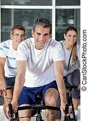 Three People On Exercise Bikes - Portrait of three happy...