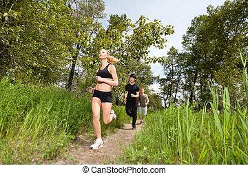 Three people running on pathway