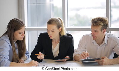 Three people sit at white table in office and discuss plan of building.