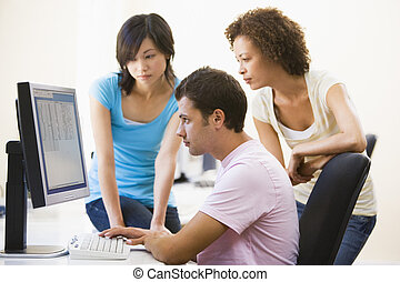Three people sitting in computer room looking at monitor