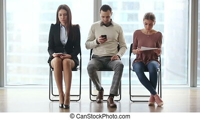 Three people waiting for job interview