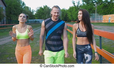 Three people walking in a park, getting some exercise. Slow...