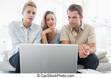 Three people working on computer
