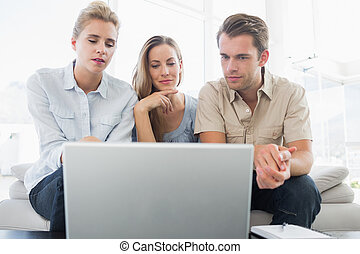Three people working on computer