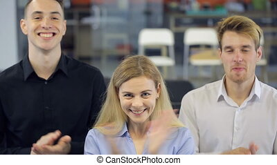 Three persons happily clap their hands to express delight....