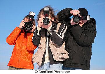 three photographers against blue sky