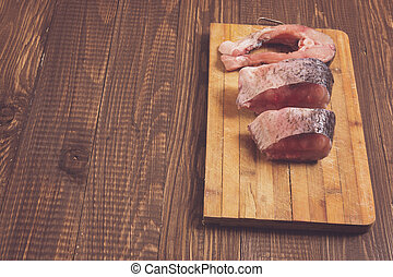 Three pieces of fish are on plank