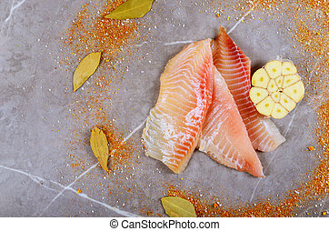 Three pieces of fresh tilapia on marble board